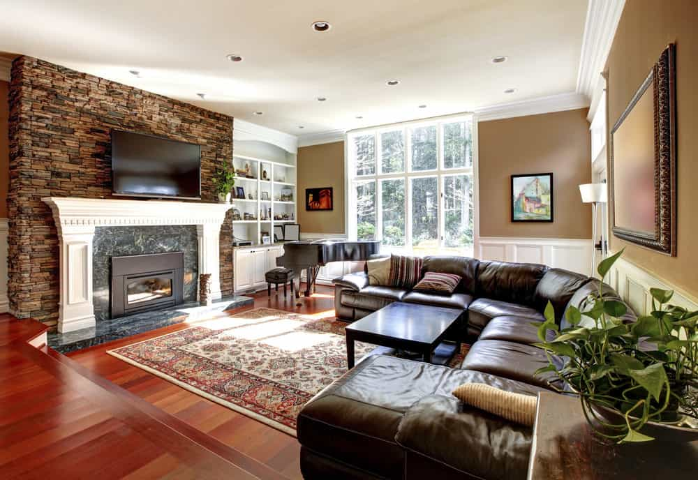 This living room features a large fireplace with a widescreen TV just above it. The room also offers a curved brown leather sofa set.