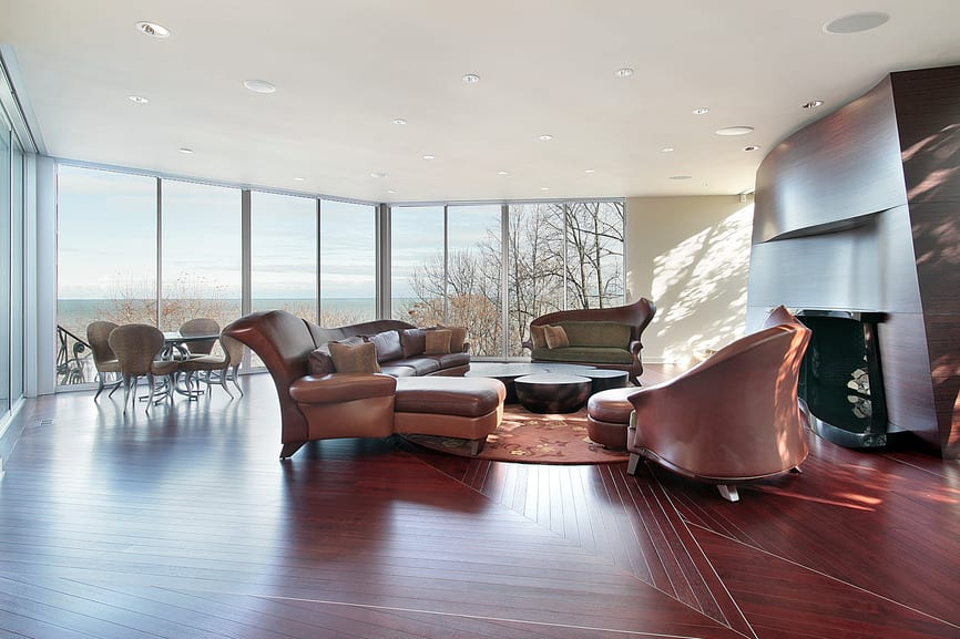 A large contemporary living room featuring reddish hardwood flooring and a brown sofa set, along with a large modern fireplace.