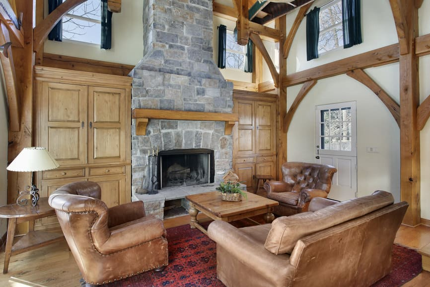 This formal living room offers a brown sofa set and a square center table, along with a stone fireplace.