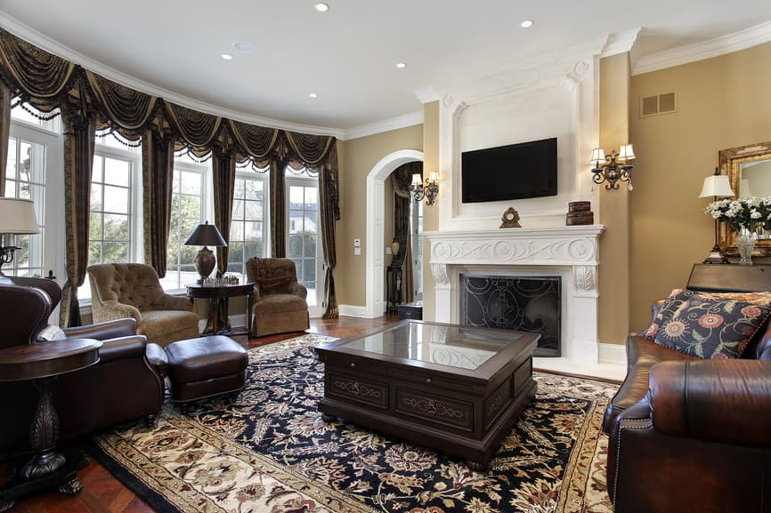 Large family living room boasting elegant leather seats along with a classy centerpiece table set on top of the gorgeous area rug covering the hardwood flooring. There's a fireplace and a flat-screen TV as well.