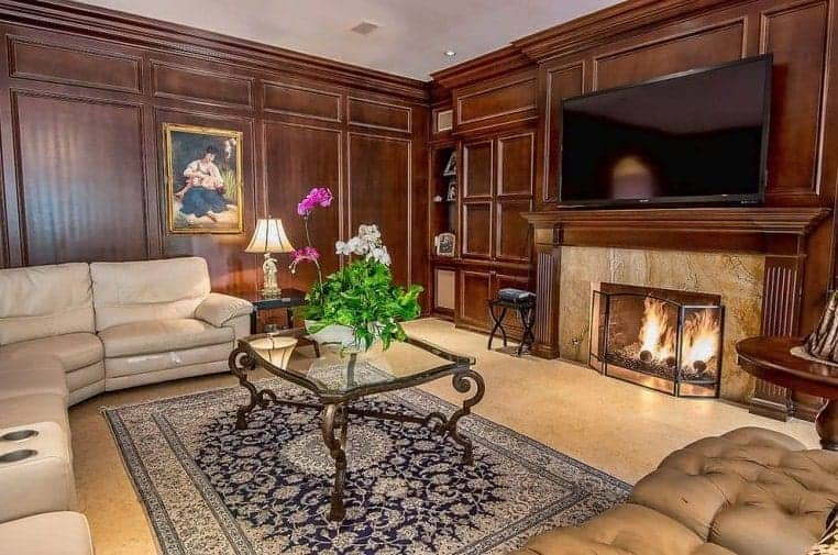 Large brown formal living room with a comfortable sofa set and a classy glass top center table on top of a stylish rug. There's a fireplace and a large widescreen TV set in front.