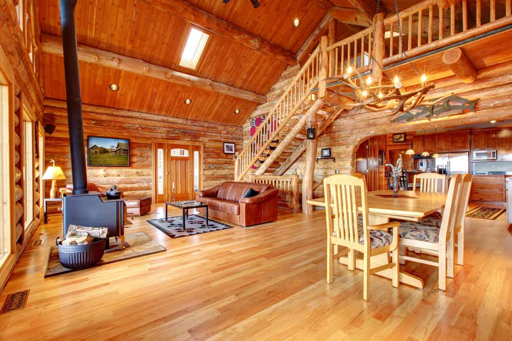 Large rustic great room with a tall wooden ceiling with logs beams. It also has logs walls and has hardwood floors. The area offers a living space with a fireplace and a square dining table set, along with a kitchen on the far side.