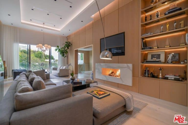 Large formal living room boasting a modern gray couch and a fireplace, along with a widescreen TV on the wall. The area offers a built-in shelving and a white tray ceiling.