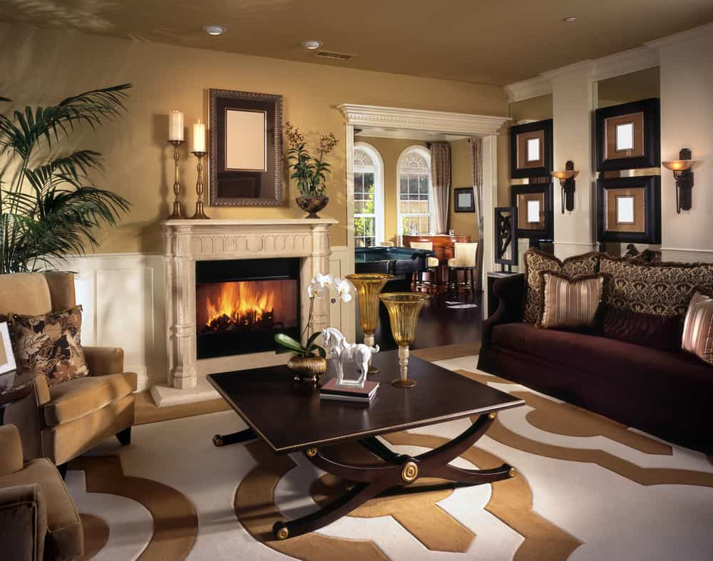 A formal living room with an elegantly-designed area rug along with brown walls and ceiling. The room offers a fireplace and a cozy sofa set, along with a stylish center table.