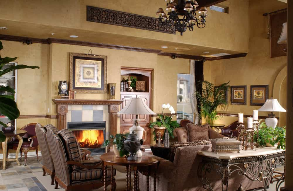 Large formal living room with brown walls and a brown sofa set, along with a gorgeous fireplace and a fancy chandelier.