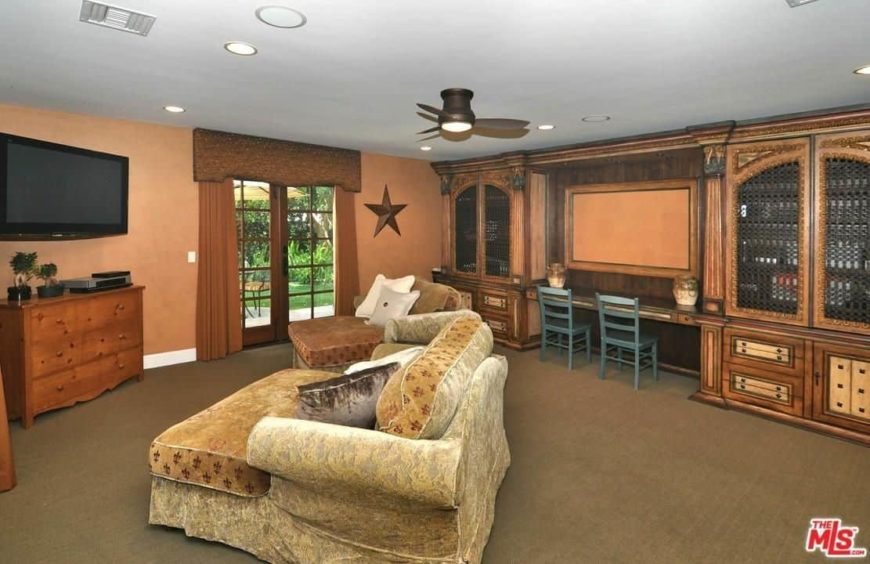 Brown living space featuring a regular white ceiling and brown carpet flooring. The room offers a large and elegant couch with a TV set in front.