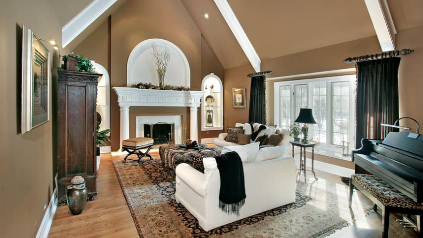 Large formal living room boasting brown walls and a vaulted ceiling with white beams. The room boasts white couches and a fireplace, along with a classy black piano on the side.