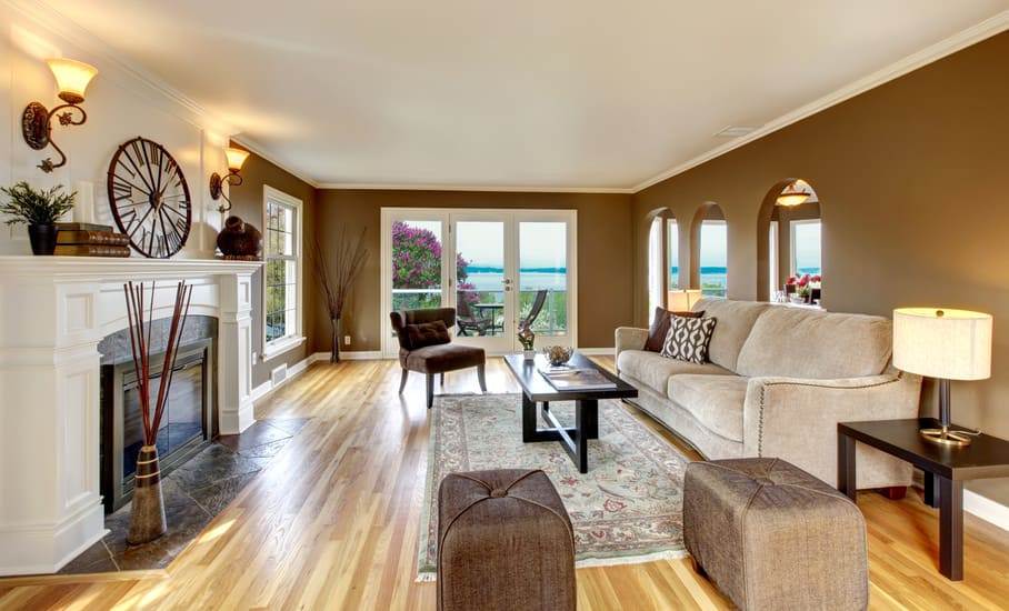 Large formal living room featuring brown walls and hardwood floors. The room offers a large comfy couch and a fireplace lighted by wall lights.