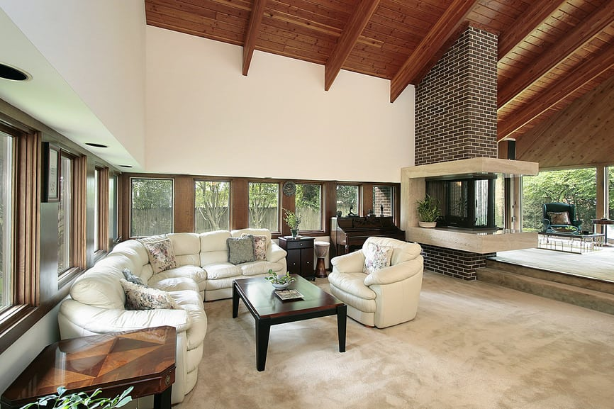 Huge formal living room featuring a white sofa set and a wooden center table set on the carpeted flooring and is under the home's high vaulted ceiling with beams. The area offers a piano and a large and stylish fireplace.