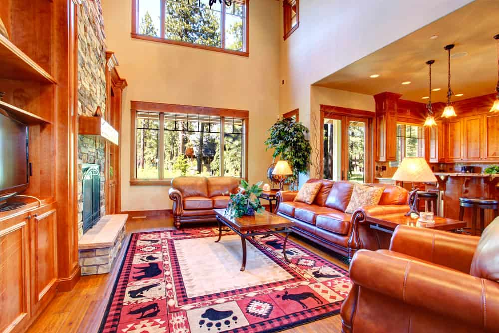 Large formal living room boasting elegant brown seats and a center table set on the room's gorgeous area rug. The room also offers a large stone fireplace with a TV beside it.