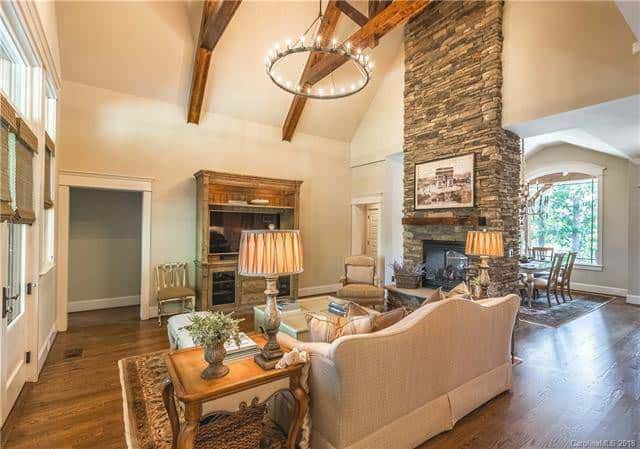 The living room has a tall two-story cathedral ceiling with the same beige tone as the walls. This makes the dark wooden exposed beams stand out illuminated by the round chandelier hanging over the coffee table.
