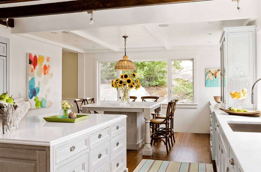 Bright kitchen decorated with lovely artworks that are mounted on the beadboard walls. It has a double kitchen island and white cabinets along with a charming striped rug that lays on the wide plank flooring.