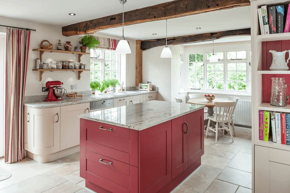 A red breakfast island adds a striking accent in this airy kitchen with limestone flooring and regular ceiling lined with rustic beams. There's a round dining set by the white-framed windows lighted by a glass dome pendant.