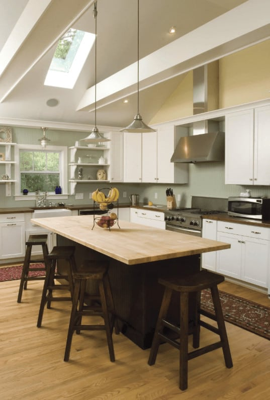 High ceiling kitchen features a skylight and chrome pendant lights that hung over the black breakfast bar paired with dark wood stools. It includes white cabinetry and classic runners that lay on the hardwood flooring.