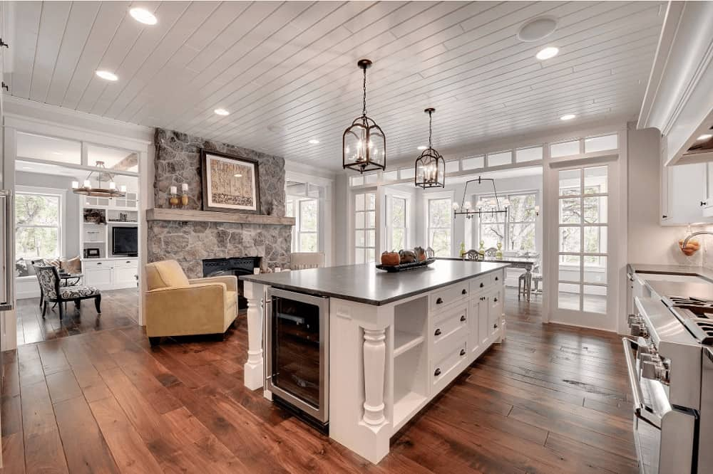 A pair of lantern pendants along with recessed lights fitted on the shiplap ceiling illuminate this spacious kitchen offering stainless steel appliances and a white center island with built-in storage and wine fridge.