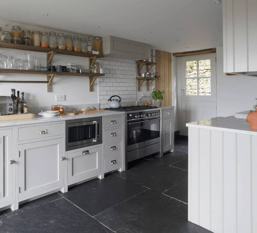 This kitchen boasts gray cabinetry and a stainless steel range under subway tile backsplash. It has black tiled flooring and white walls mounted with wooden floating shelves.