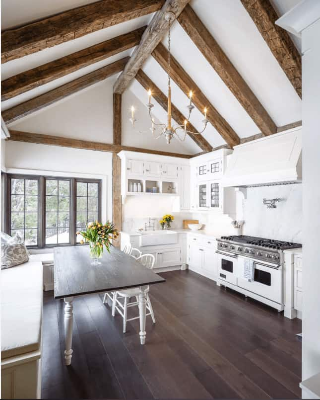 White eat-in kitchen with wide plank flooring and a cathedral ceiling lined with rustic wood beams. It includes a candle chandelier and a wooden dining table paired with round back chairs.