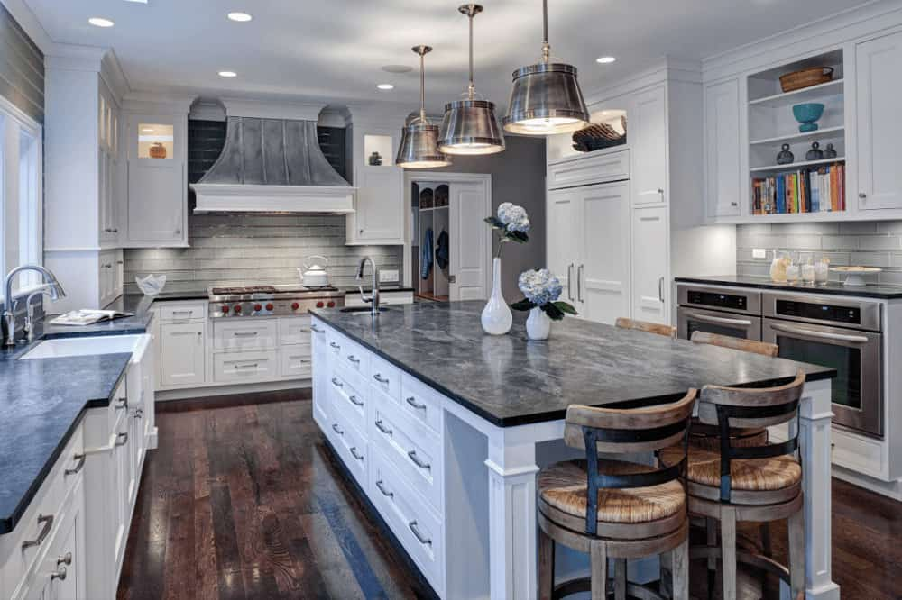 Large dome pendants hang over the immense kitchen island paired with wooden round chairs. It is surrounded by stainless steel appliances and white cabinetry topped with black countertops.