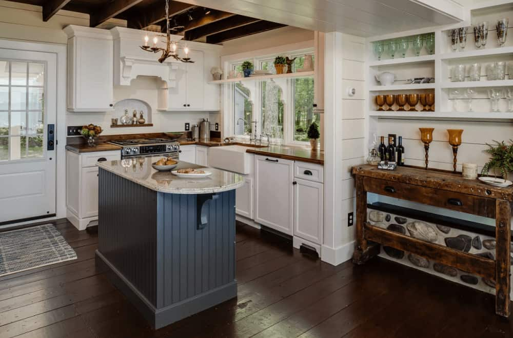 A gray beadboard island stands out against the white cabinetry and shiplap walls. This kitchen showcases a rustic buffet table and a vintage chandelier that hung from the wood beam ceiling.