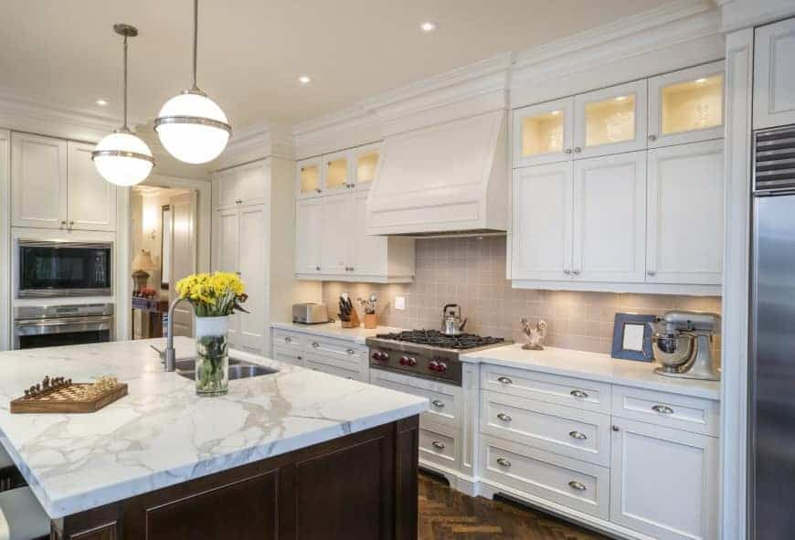 Cottage kitchen with inset appliances and white cabinetry contrasted by a dark wood breakfast island that's topped with a marble counter and dual sink. It is illuminated by glass globe pendants and recessed ceiling lights.
