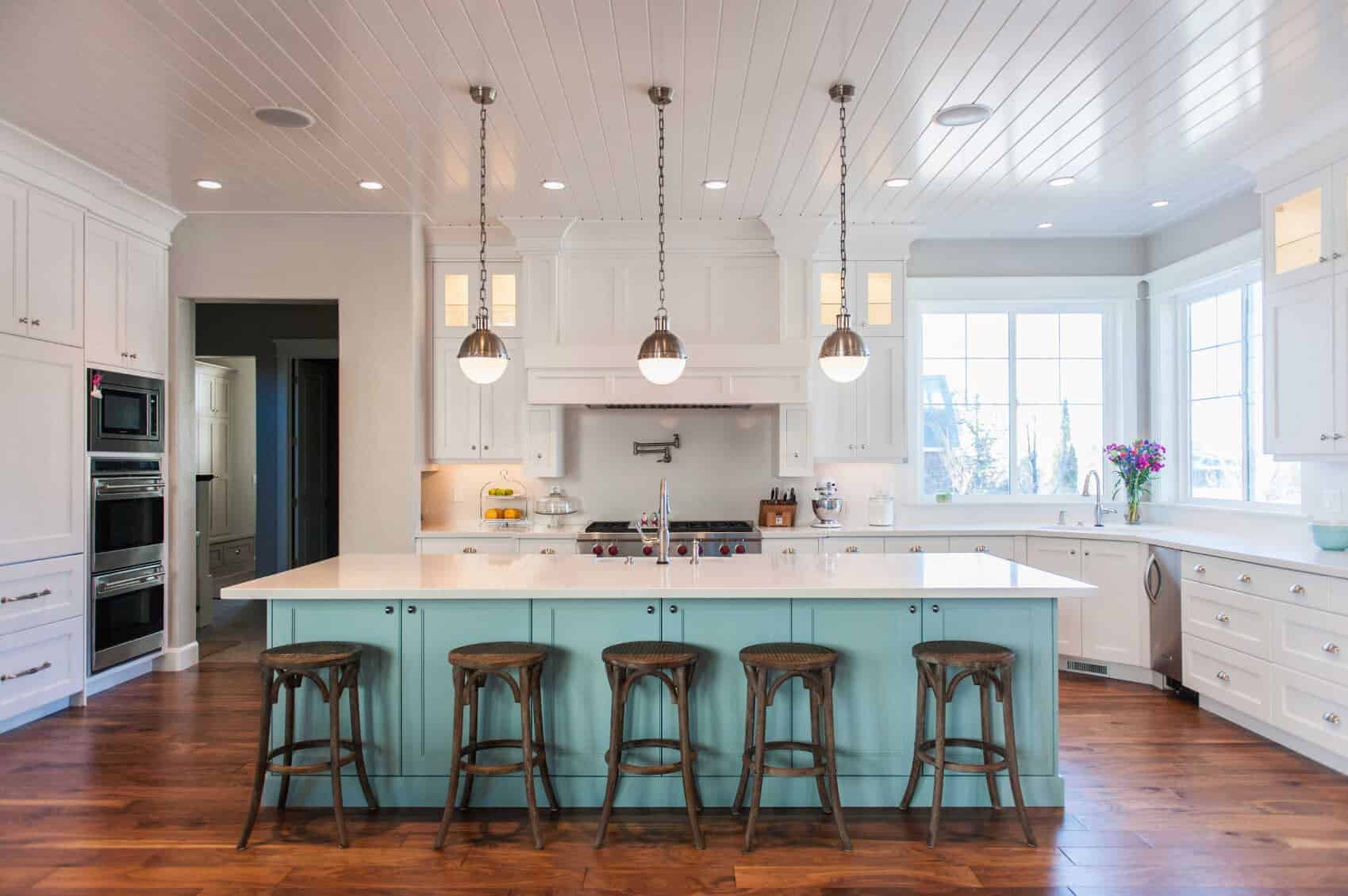 An aqua island bar lined with wooden bar stools adds a nice accent in this white kitchen with rich hardwood flooring and framed windows bringing plenty of natural light in. It includes a shiplap ceiling mounted with recessed lights and chrome pendants.