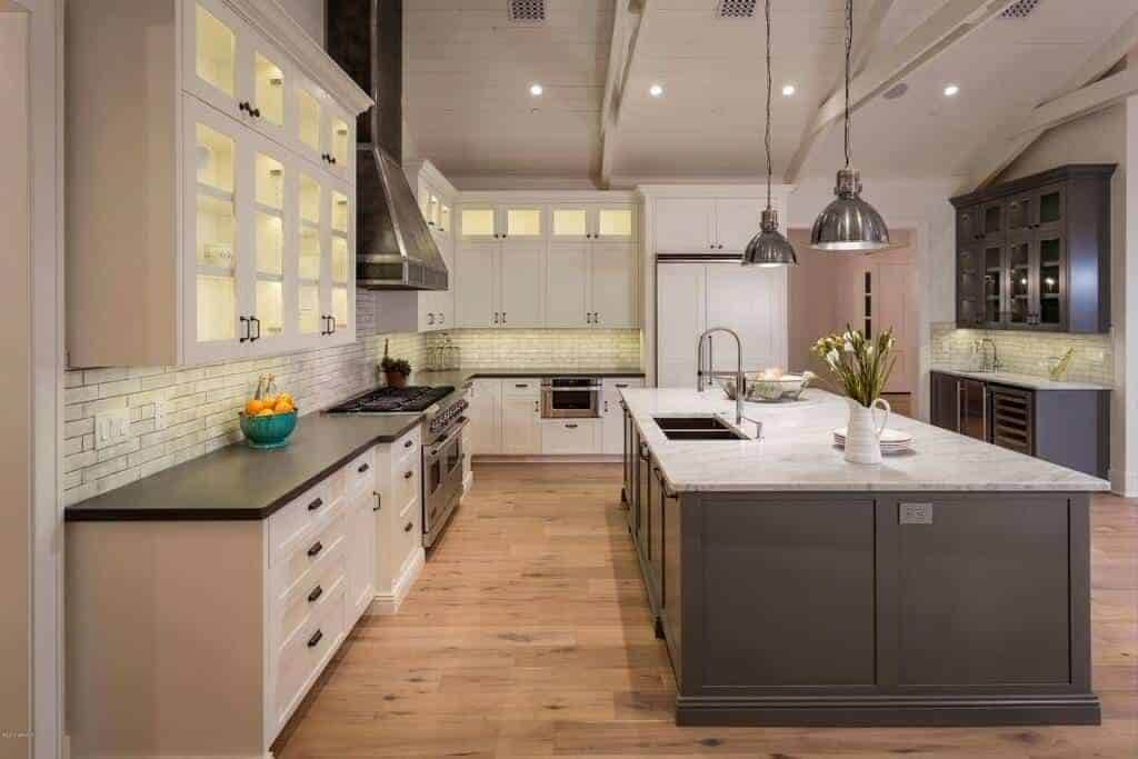 Chrome pendant lights illuminate the gray breakfast island that's fitted with dual sink and a gooseneck faucet. It is accompanied by white cabinetry and black range hood against the brick backsplash.