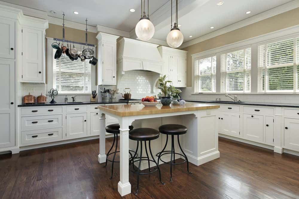 Wrought iron stools sit at a white breakfast island topped with a light wood counter. It is illuminated by a pair of glass globe pendants and recessed ceiling lights.