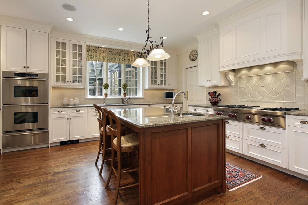 Warm kitchen features white cabinetry and a wooden island bar fitted with a round sink and chrome fixtures. It is accompanied by glass dome pendants and cushioned counter chairs that blend in with the hardwood flooring.