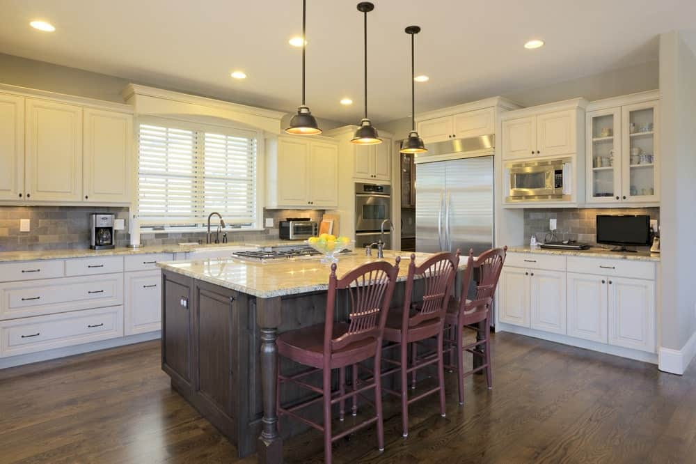 Burgundy chairs sit at a dark wood kitchen island lighted by black dome pendants. It is surrounded by stainless steel appliances and white cabinetry against the stone brick backsplash.