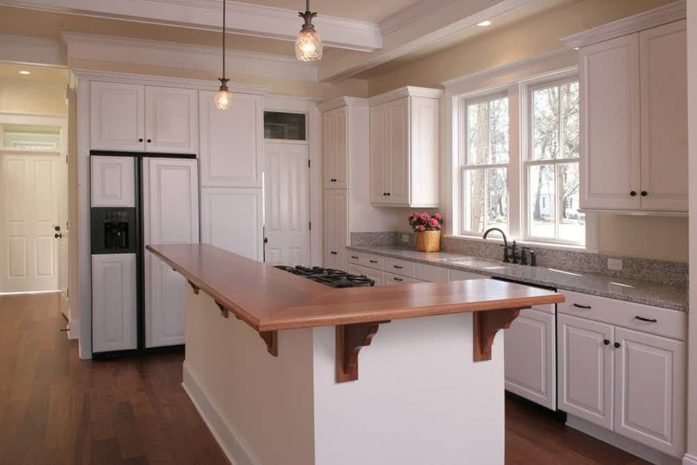 A pair of glass dome pendants hang over the kitchen island topped with an L-shaped eating counter. It is accompanied by white cabinetry and a framed window that invites natural light in.