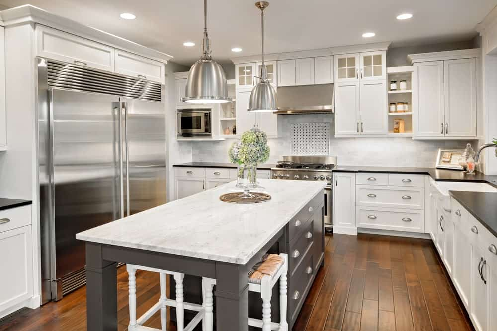 Stainless steel appliances complement the chrome pendant lights that hung over the gray breakfast island topped with white marble counter. It is accompanied by white cabinetry and bar stools over wide plank flooring.