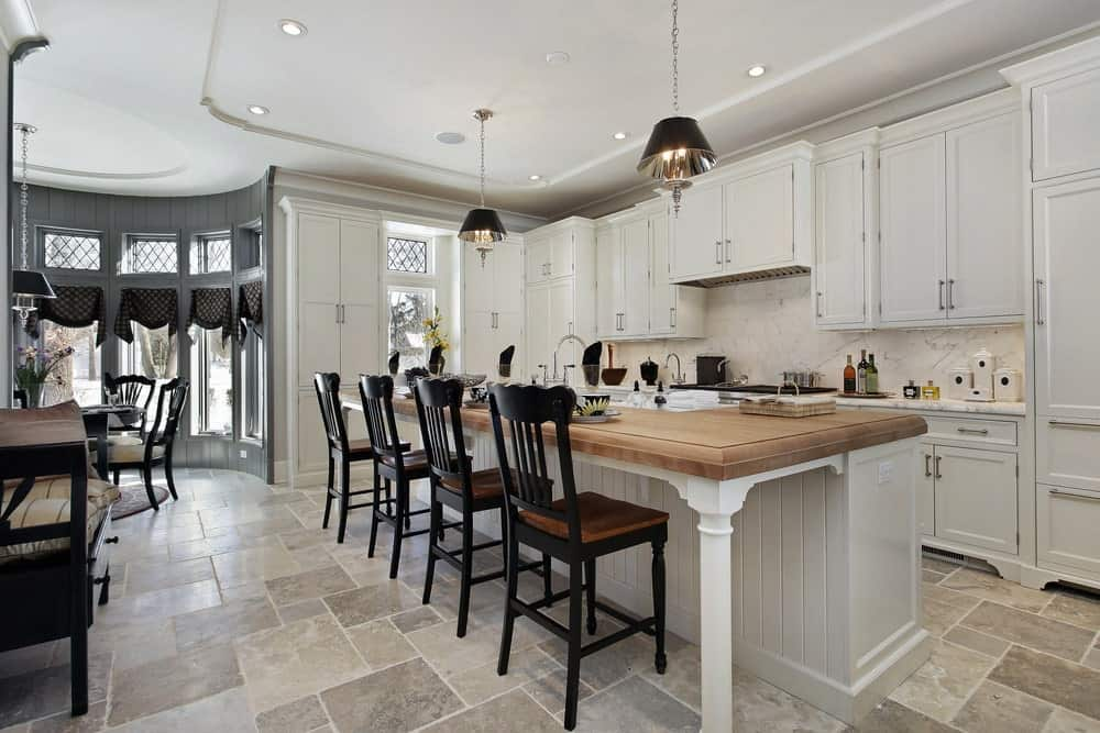 Cottage kitchen with limestone flooring and tray ceiling mounted with recessed lights and black dome pendants. It includes white cabinetry and a beadboard breakfast bar lined with black counter chairs.
