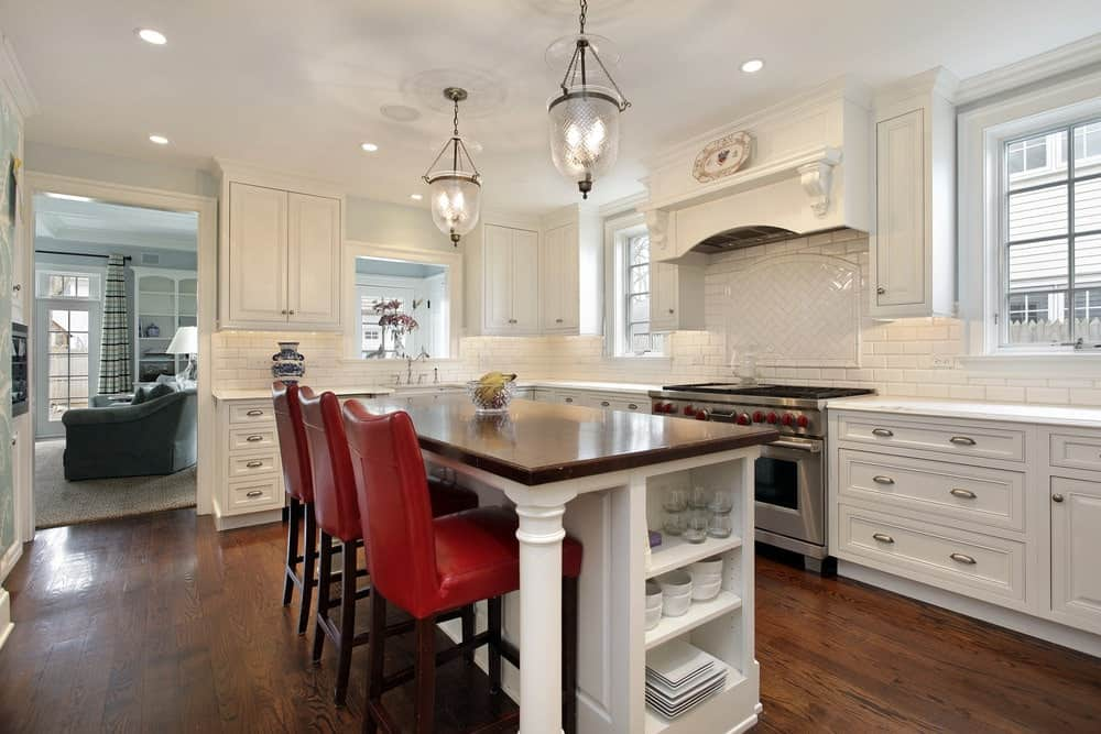 Red leather chairs stand out in this kitchen with white cabinetry and a breakfast island illuminated by glass pendant lights. It boasts a stainless steel range with an alcove hood designed with a decorative plate above the mantel.