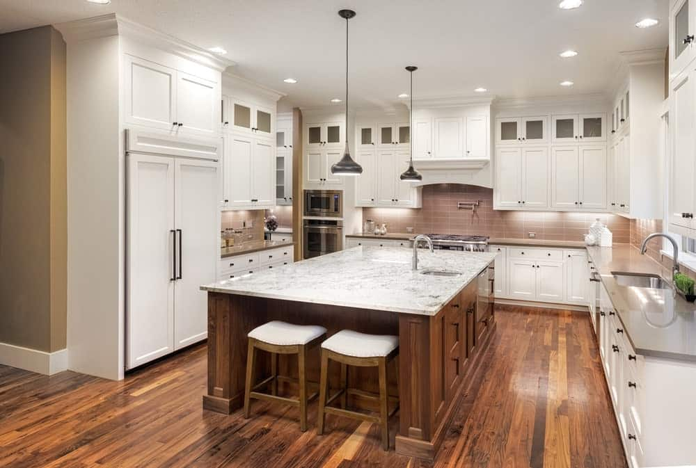 White cabinetry and inset appliances surround an immense central island fitted with a sink and chrome faucet. It is paired with white cushioned stools that blend in with the hardwood flooring.