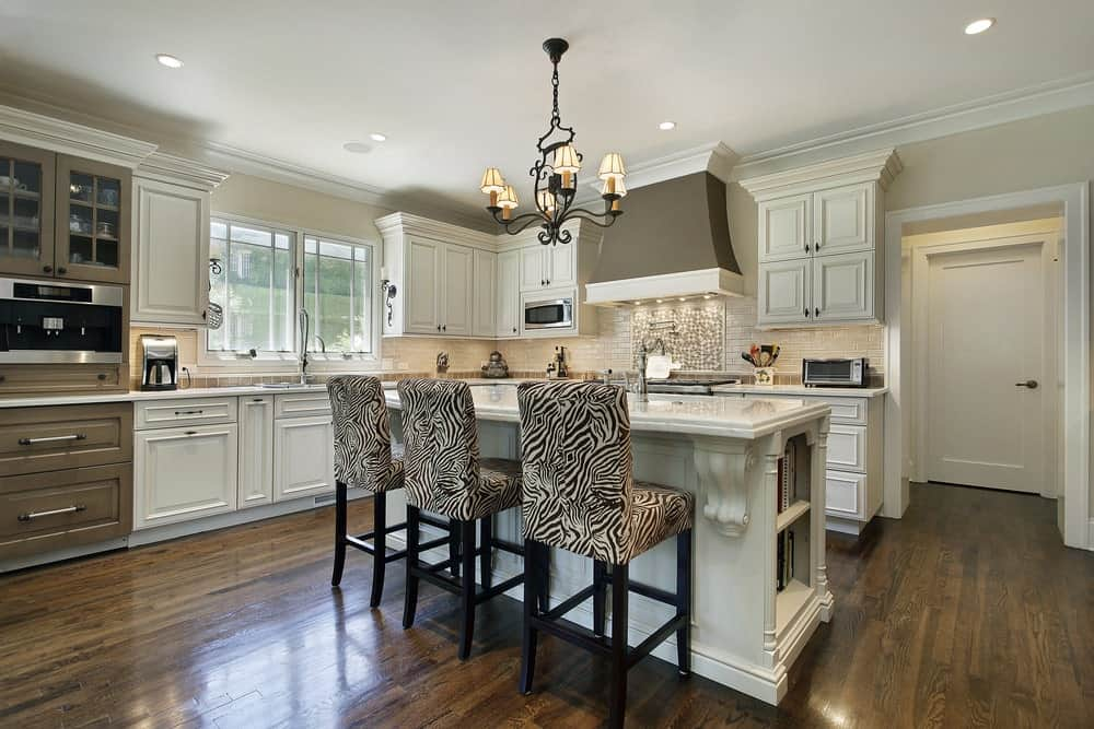 An ornate chandelier hangs over the kitchen bar lined with zebra counter chairs. It is accompanied by white cabinetry and a gray vent hood fixed above the subway backsplash tiles.