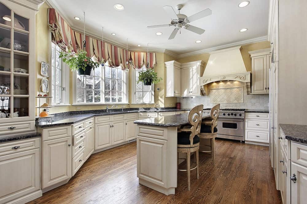 Homey kitchen features black granite countertops and white cabinetry matching with the island bar that's paired with stylish wooden chairs. It has natural hardwood flooring and framed windows dressed in red striped valances.