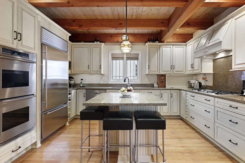 White cabinetry with inset appliances surrounds a beadboard center island paired with black leather cushioned stools. It is illuminated by a stylish pendant light that hung from the wood beam ceiling.