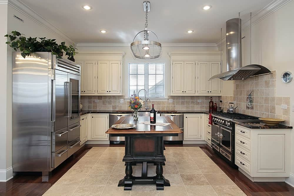 A tiled floor centerpiece complements the beige backsplash tiles fixed above the black granite countertops. This kitchen features white cabinetry and a dark wood breakfast island with stainless steel pot rack overhead.
