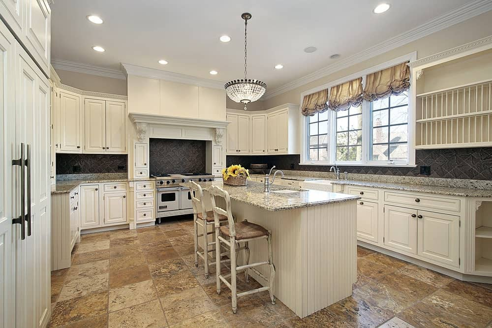 A fancy glass pendant along with recessed ceiling lights illuminate this kitchen showcasing white cabinetry and beadboard central island paired with distressed counter chairs.
