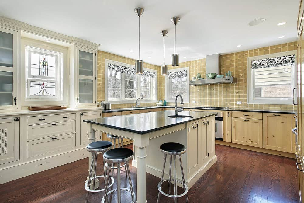 This kitchen offers a white breakfast bar with round metal stools along with light wood cabinetry that complements the backsplash tiles mounted with a stainless steel vent hood.
