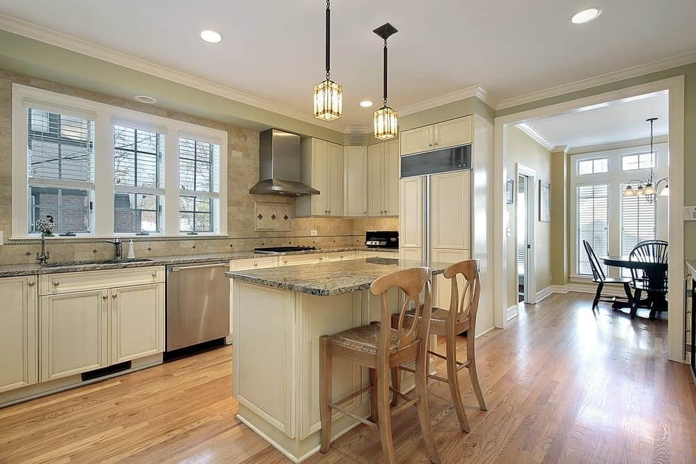 Ambient light from the pendant and recessed ceiling lights create a warm and cozy feel in this kitchen with white cabinetry and a matching island bar accompanied by wooden counter chairs.
