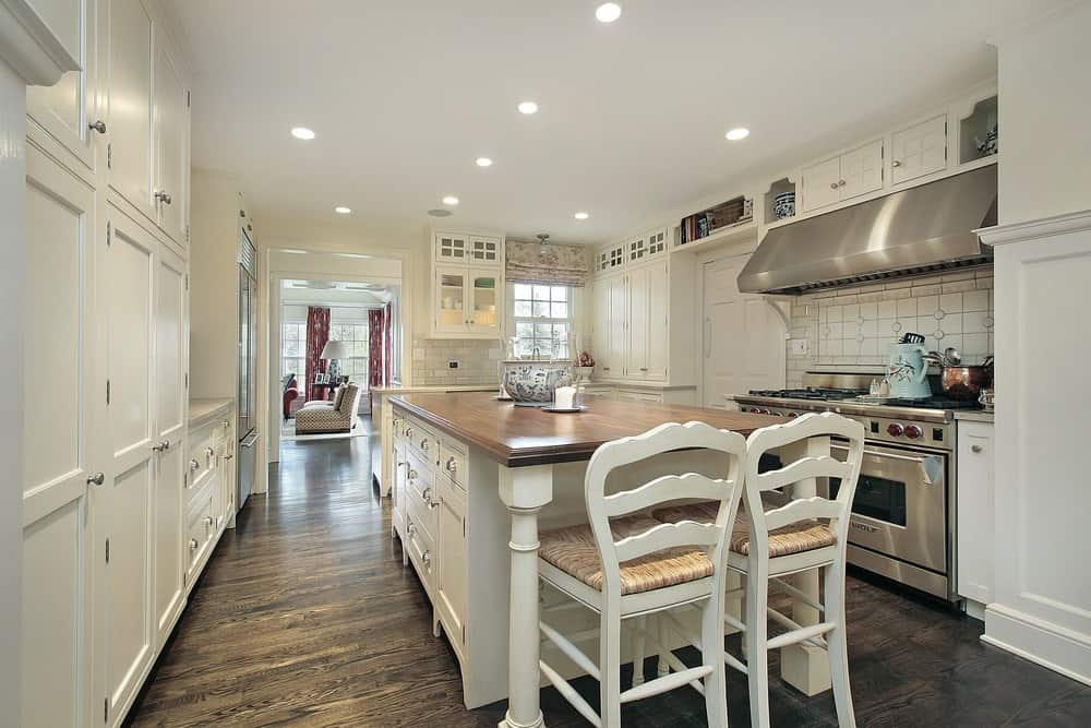White cushioned chairs sit at a central island topped with a smooth wooden counter. It is surrounded by white cabinetry and stainless steel appliances.