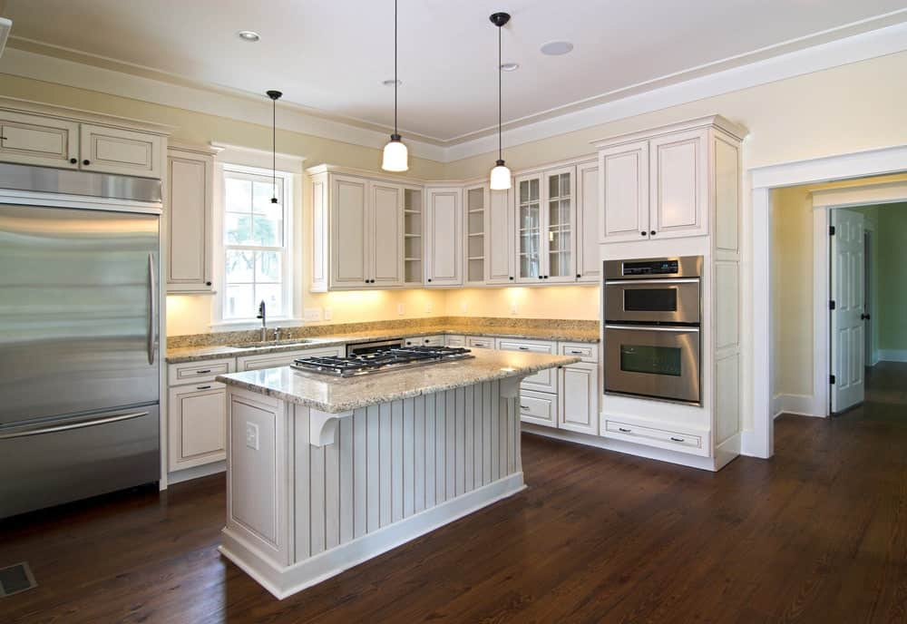 Simple kitchen boasts white cabinetry and a beadboard breakfast bar fitted with a built-in cooktop. It includes mini pendant lights and inset appliances in stainless steel.