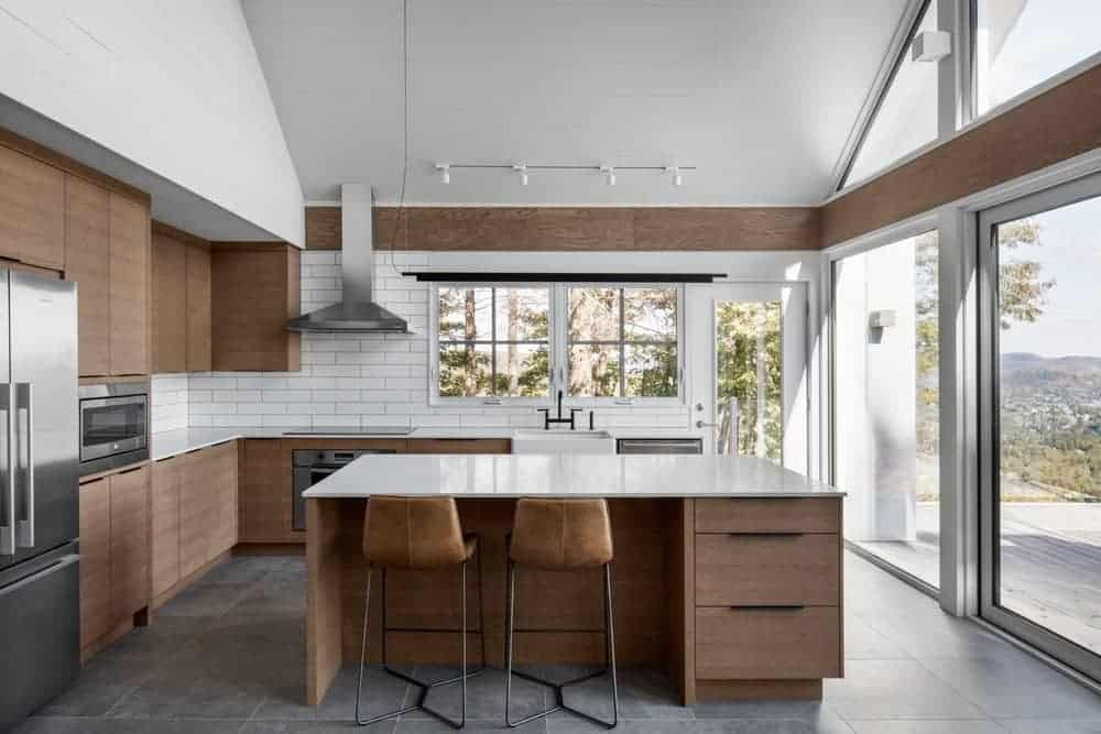 Bright kitchen with concrete tiled flooring and glazed windows overlooking the outdoor scenery. It has a wooden central island and cabinetry fixed against the white subway backsplash tiles.