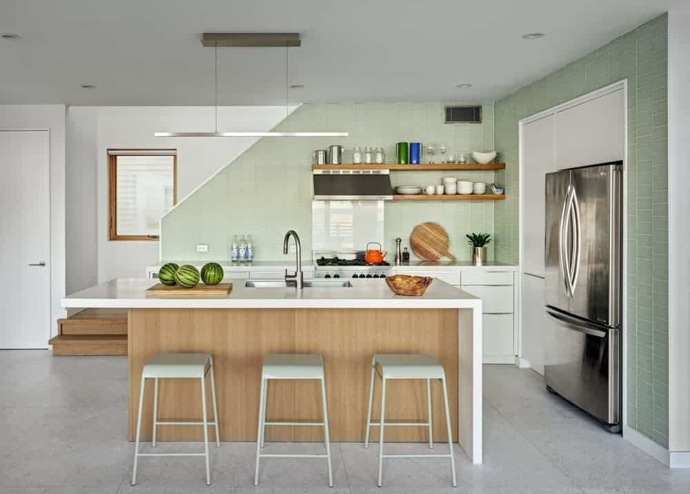 Cottage kitchen with concrete flooring and green tiled walls fitted with inset cabinetry and appliances. There's a breakfast bar in the middle lined with sleek stools.