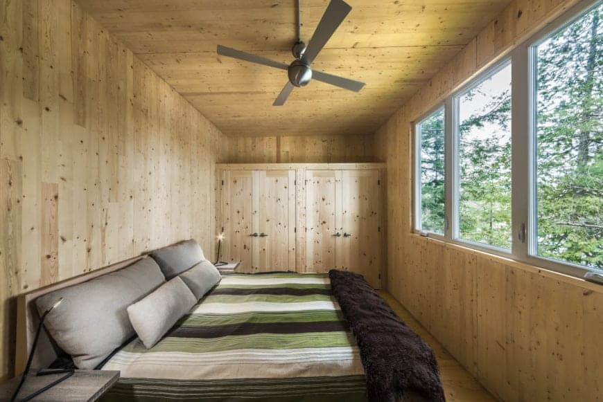 This Cottage-style bedroom has a uniform tone on its wooden walls, floors and ceiling that has a metal modern ceiling fan over the wooden bed that has a green striped bed sheet and gray pillows that are lightened by the row of glass windows across from the bed.