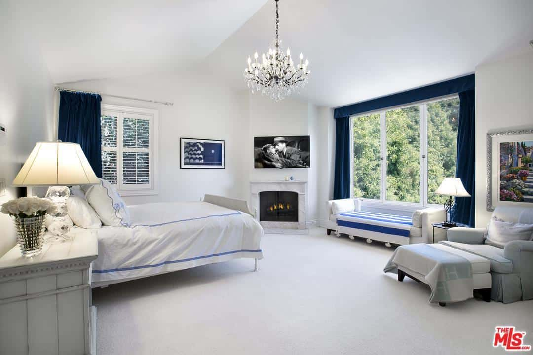 This spacious and bright Cottage-style primary bedroom has a white cathedral ceiling, white walls, white bed and even a white fireplace with a matching white mantle. These are all complemented by the blue elements scattered across the room.