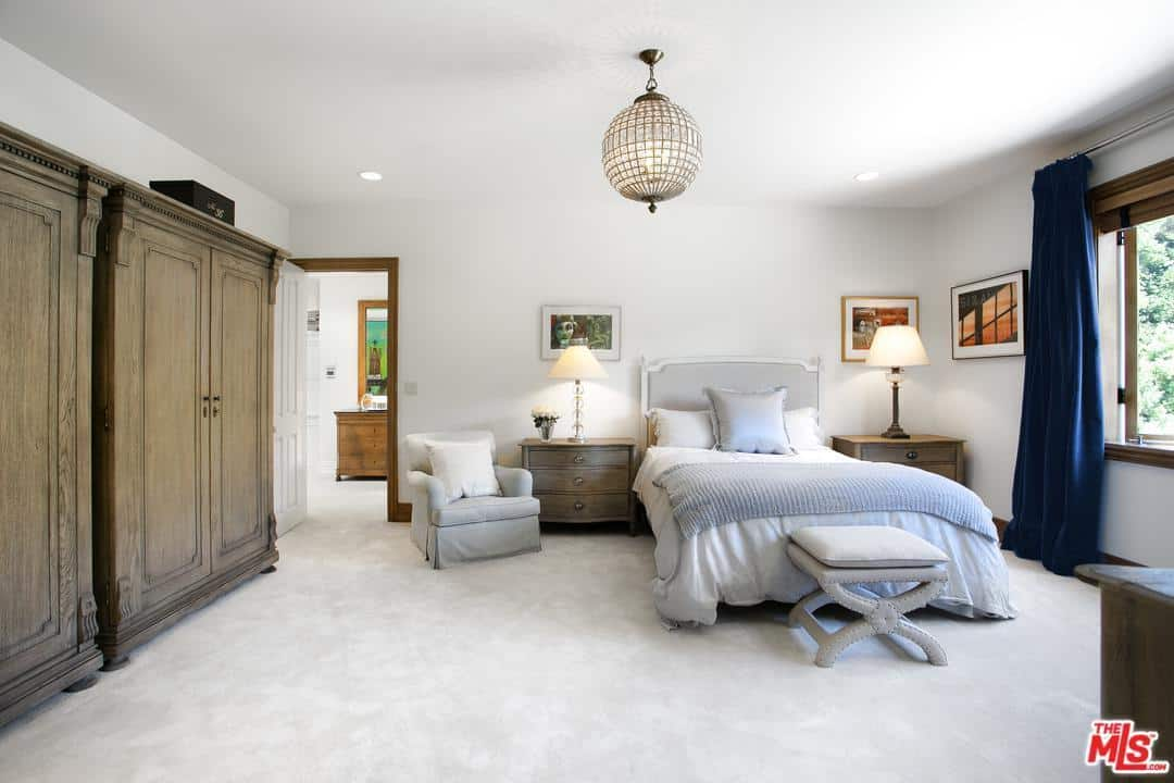 The bright elements of this Cottage-style bedroom make the brown wooden cabinets and bedside drawers stand out. These also pair well with the spherical decorative pendant light hanging from the white ceiling with recessed lights at the corners.