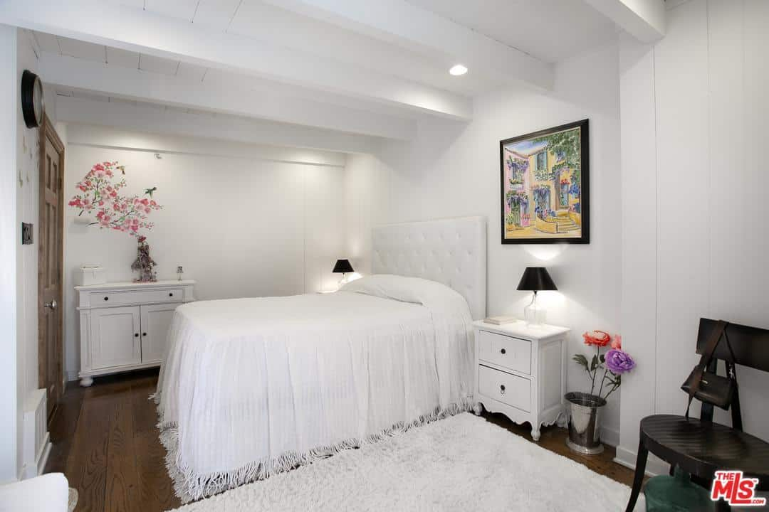 The white wooden ceiling of this Cottage-style bedroom has exposed wooden beams that match well with the white walls and white bed with a white cushioned headboard. These white elements serve as a nice background for the painting and colorful flower decorations.