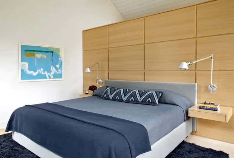 The gray bed and its gray sheets and pillows pair well with the furry navy blue area rug underneath and the large wooden panel behind its gray headboard. This panel has built-in shelves that serve as bedside tables topped with wall-mounted lamps.